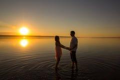 Le jeune couple tient des mains dans l'eau sur la plage d'?t? Coucher du soleil au-dessus de la mer Deux silhouettes contre le so photo stock