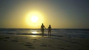 Le jeune couple tient des mains et marche au coucher du soleil sur la plage sablonneuse d'or Hippie deux dans l'amour, promenades banque de vidéos