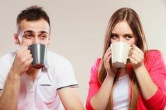 Le jeune couple tient des tasses avec le thé ou le café Image stock