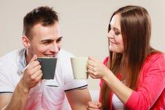 Le jeune couple tient des tasses avec le thé ou le café Images libres de droits