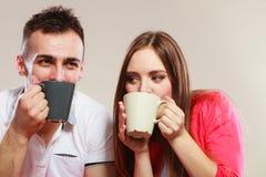 Le jeune couple tient des tasses avec le thé ou le café Photo libre de droits