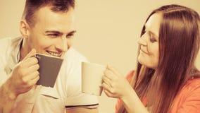 Le jeune couple tient des tasses avec le thé ou le café Photographie stock libre de droits
