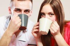 Le jeune couple tient des tasses avec le thé ou le café Image libre de droits