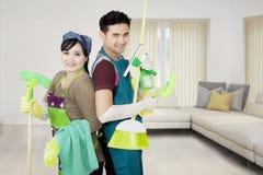 Le jeune couple tient l'équipement de nettoyage Photographie stock