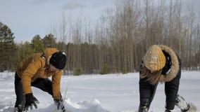 Le jeune couple a un combat de boule de neige dans la forêt d'hiver banque de vidéos