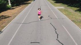 Le jeune coureur féminin mince dans les vêtements de sport roses s'exerce en parc vert de ville Formation dur Fille attirante fol banque de vidéos