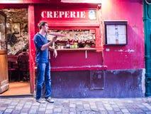 Le jeune cuisinier masculin tournoie la casserole de crêpe devant son creperie sur Montmartre Photos libres de droits