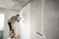 Le jeune dépanneur aligne avec la spatule en plastique Travailleur collant des papiers peints sur le mur en béton R?parez l'appar photo libre de droits