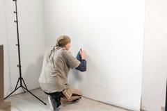 Le jeune dépanneur aligne avec la spatule en plastique Travailleur collant des papiers peints sur le mur en béton R?parez l'appar photo stock