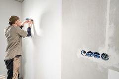 Le jeune dépanneur aligne avec la spatule en plastique Travailleur collant des papiers peints sur le mur en béton R?parez l'appar photographie stock