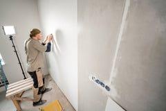 Le jeune dépanneur aligne avec la spatule en plastique Travailleur collant des papiers peints sur le mur en béton R?parez l'appar images stock