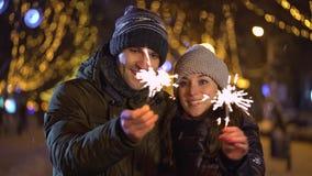 Le jeune dans des couples d'amour dessine le coeur avec des cierges magiques dans le ciel banque de vidéos