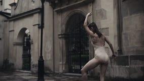 Le jeune danseur féminin professionnel exécute la danse acrobatique le long de la rue médiévale sous la pluie Filles humides banque de vidéos