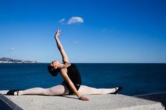Le jeune danseur souple fait les fentes sur un grand bloc en pierre Image libre de droits