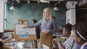 Le jeune directeur féminin blond motive des collègues de métis pour travailler Le meneur d'équipe présente des données financière Photo stock