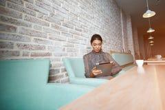 Le jeune directeur féminin magnifique du café moderne fait le nouveau menu sur le comprimé numérique portatif, Images stock