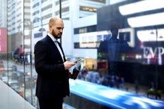 Le jeune directeur qualifié masculin utilise le téléphone de cellules pendant la coupure au travail Photo libre de droits