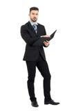 Le jeune directeur sûr tenant des affaires classe avec des écritures Image stock