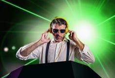 Le jeune DJ attirant et frais dans la chemise et des bretelles remélangeant la musique à la boîte de nuit utilisant des écout photographie stock libre de droits