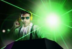 Le jeune DJ attirant et frais dans la chemise et des bretelles remélangeant la musique à la boîte de nuit utilisant des écout photographie stock