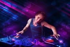 Le jeune DJ jouant sur des plaques tournantes avec des effets de la lumière de couleur Photo stock