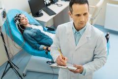 Le jeune docteur agréable faisant des notes au sujet des patients conditionnent Photo libre de droits