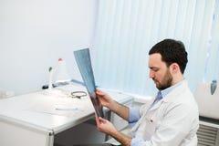 Le jeune docteur caucasien d'homme examine l'image IRM de la tête humaine dans le bureau Images stock