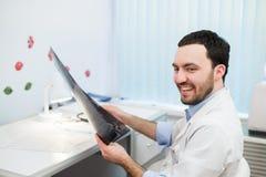 Le jeune docteur caucasien d'homme examine l'image IRM de la tête humaine dans le bureau regardant le patient et le sourire Photo stock