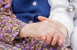 Le jeune docteur doux retient la main de dame âgée Photographie stock libre de droits