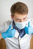 Le jeune docteur faisant des pouces lèvent le signe Photos libres de droits