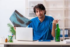 Le jeune docteur masculin buvant dans le bureau photos libres de droits