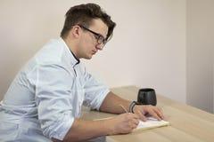 Le jeune docteur masculin caucasien dans un équipement blanc écrit quelque chose qui se repose sur la table avec la tasse de thé  image libre de droits