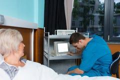 Le jeune docteur masculin dans l'uniforme regarde le moniteur du De médical Photo stock