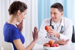 Le jeune docteur propose la pomme de collègue images libres de droits