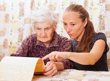 Le jeune docteur retient la main de dame âgée Photo stock