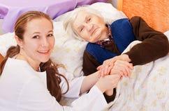 Le jeune docteur retient les mains de femme âgée Photographie stock