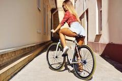Le jeune dos sexy de femme sur le sport a fixé la bicyclette de vitesse posant sur l'outd images libres de droits