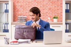 Le jeune employé bel travaillant dans le bureau image stock