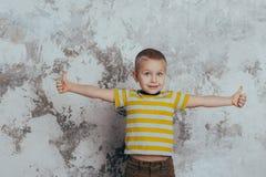 Le jeune enfant de gar?on dans un T-shirt ray? jaune c?l?brant un rire de sourire heureux avec une main a r?parti image libre de droits