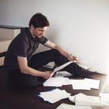 Le jeune entrepreneur masculin fait la séance de réflexion se reposant sur le plancher dans l'appartement Approche créative aux a images libres de droits