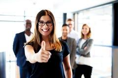 Le jeune exécutif femelle faisant des pouces lèvent le signe Image libre de droits