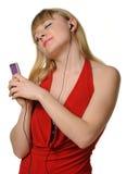 Le jeune femme écoute la musique d'un joueur Photographie stock libre de droits
