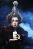 Le jeune femme avec créateur composent Une grande toile d'araignée avant de lune lumineuse étrange Image libre de droits
