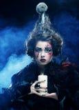 Le jeune femme avec créateur composent Une grande toile d'araignée avant de lune lumineuse étrange Image stock