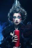 Le jeune femme avec créateur composent Une grande toile d'araignée avant de lune lumineuse étrange Images stock