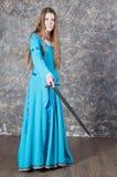 Le jeune femme avec le long cheveu pose avec l'épée Photographie stock libre de droits