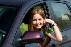 Le jeune femme avec le véhicule neuf Photographie stock libre de droits