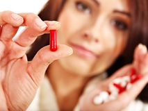 Le jeune femme ayant la grippe prend des pillules. Image stock