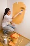Le jeune femme colore son plat Photographie stock