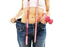 Le jeune femme dans de vieux jeans halètent après poids perdant Photo stock
